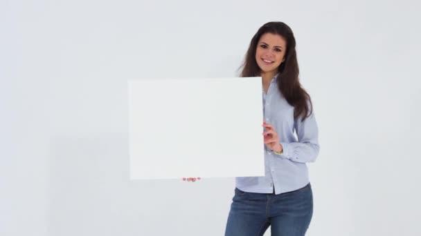 Usmívající se krásná dívka při pohledu na fotoaparát a drží prázdná bílá transparent