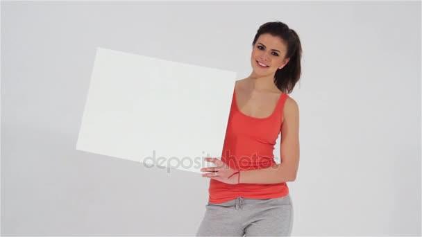 Sportovní dívka držící prázdný bílý nápis ve svých rukou a při pohledu na fotoaparát