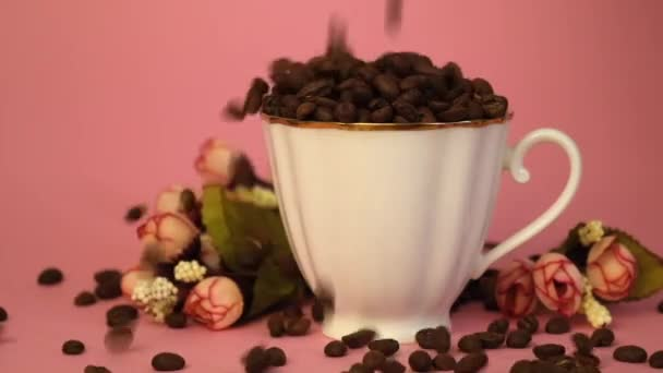 Roasted coffee beans poured into a white cup. Porcelain cup full of coffee beans and flowers on pink background. Slow motion.