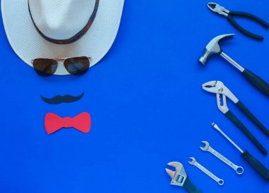 Happy Fathers Day and tools colorful tie and hat on blue background. Place for the text. Top view.