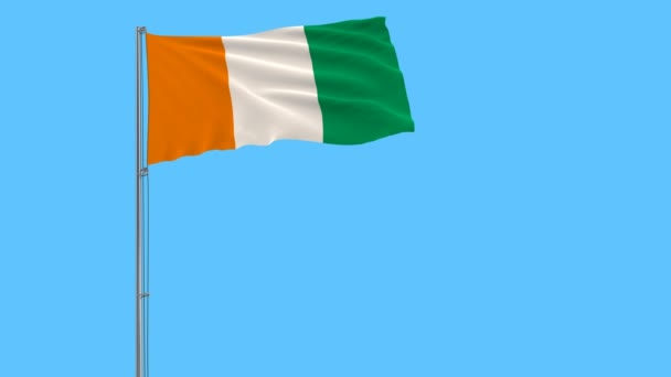 Flag of Ivory Coast on flagpole fluttering in the wind on blue background, 3d rendering