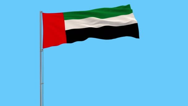 Isolate flag of United Arab Emirates on a flagpole fluttering in the wind on a blue background
