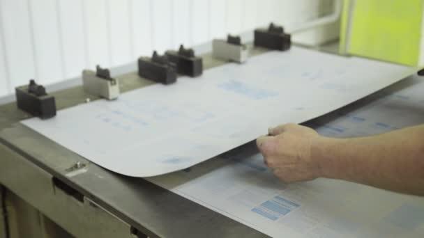 Detailní záběr rukou děrovačky pracující uvnitř tiskárny