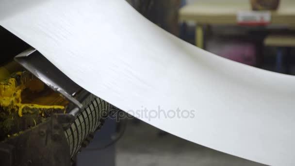 Dlouhá role papíru visí, tahání z jedné části zařízení do jiného