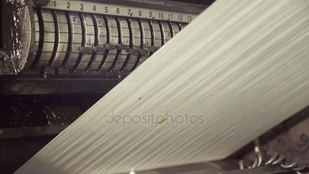Dlouhé nestříhané papíru na válcování stroj, pohybující se
