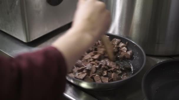 hrnec peče maso v pánvi v průmyslové kuchyni v restauraci