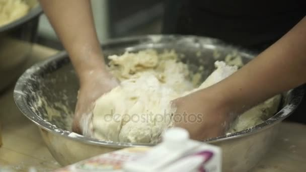 Closeup hands of cooker kneads dough in bowl in industrial kitchen