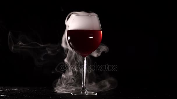 Isolated glass with wine smoke on black background