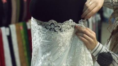 Tissue seller prepares mannequin in white lace satin in fabric store