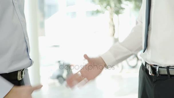Dva muži oblečení v přísné oděv potřásl rukou s sebou.