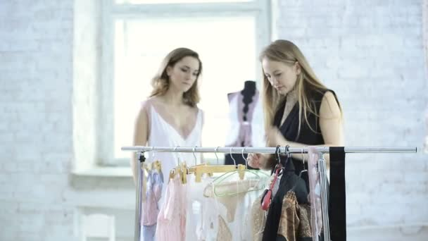 Designer helps beautiful women to choose underwear on hangers.