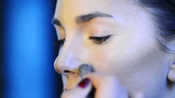 Makeup artist applies skintone foundation on beautiful face of model.