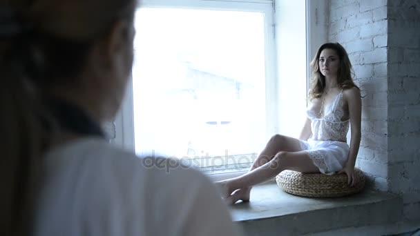 Sexy model v bílé noční košili na focení Pózuje na fotoaparát studio