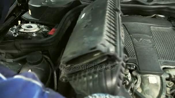Muž v rukavicích opatrně vytáhne vzduchový filtr pro výměnu.