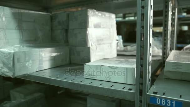 Detailní záběr rukou člověka trvá pole z poličky uvnitř skladu