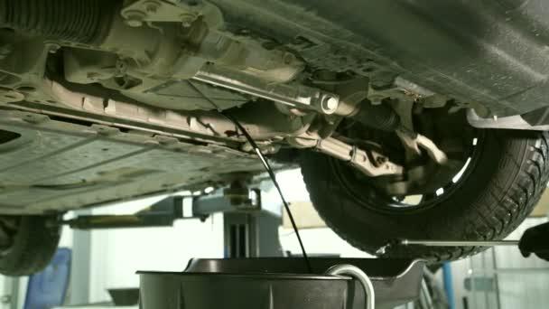 Pracovní otevře víko, ropě přitékající z dolní části auta v garáži