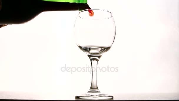Barmann füllt Glas mit alkoholischen Getränken auf Tisch im Zimmer.