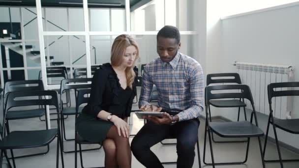 Man and woman talking, using tablet while sitting in conference room.