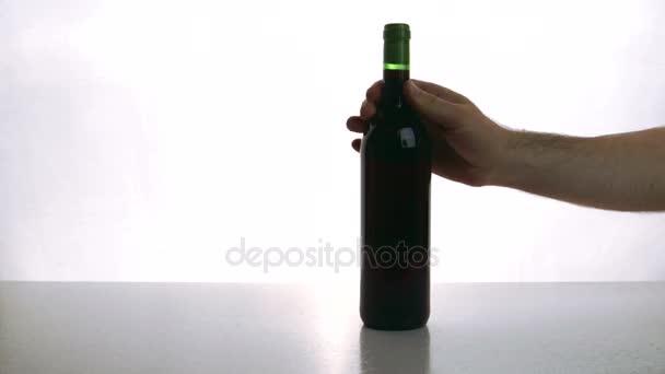 Muž a žena dát na stůl láhev červeného vína a brýle indoor