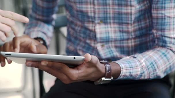 Dva lidé komunikovat pomocí tabletu, zatímco sedí v kanceláři světlo
