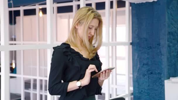 Die Porträt-Designerinnen, die Nachrichten auf ihrem Smartphone während der Pause in ihrem gemütlichen Studio liest