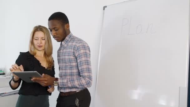 Man and woman talking, using tablet in modern office.