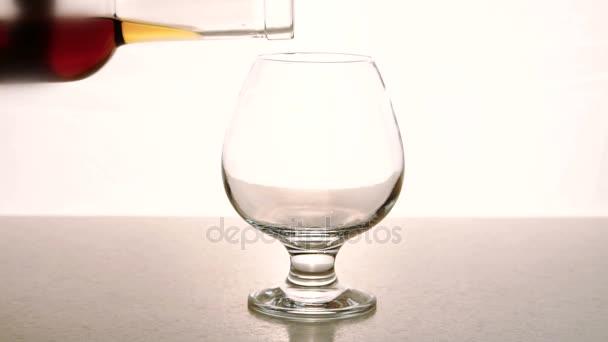 V prázdné sklenice z láhve alkoholu se nalije na bílém pozadí