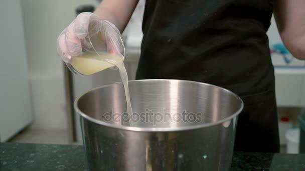 V kuchyni žena nalévá žlutá kapalina ze sklenice do hrnce