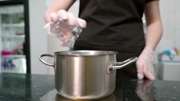 Young cook pours water and sugar into saucepan in kitchen indoors.
