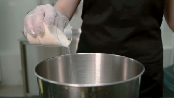 The confectioner is strewing the sugar from the plastic glass into the steel pot.