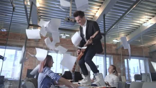 Happy successful business people in office having fun throwing documents slow motion