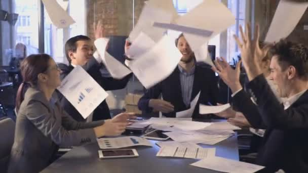 Happy successful business people in office having fun throwing documents