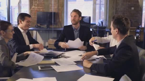 glückliche erfolgreiche Geschäftsleute im Amt, die Spaß beim Dokumentenwerfen haben