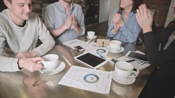 happy young business team with tablet, documents and coffee clapping hand