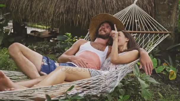 Couple in love talking, relaxing on hammock