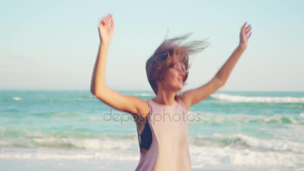 A young woman in a pink dress on beach jumping for joy and happiness. Travel concept