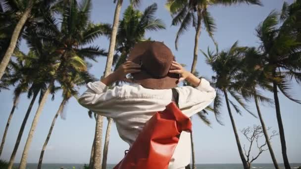 A young woman with a backpack and a hat among the coconut palms holiday is happy with the new adventures. Discoverer. Adventure Time.