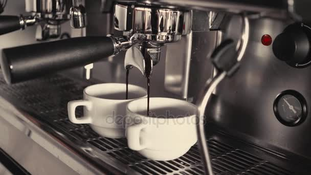 Two Cups of Coffee Being Poured from a Professional Espresso Machine. Close-Up. Concept of coffee making, service, catering