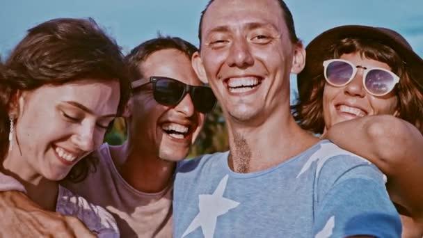 Skupina čtyř bezstarostné atraktivní happy přátelé baví venku. Koncept přátelství. Skupina s úsměvem přátel zůstat pohromadě, při pohledu na fotoaparát, všeobjímající a smál se nad ocean beach
