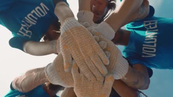 Gruppenhelfer legen ihre Hände als Symbol der Einheit und Teamarbeit zusammen