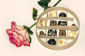 box of chocolates for the holidays and beautiful pink roses on a light background
