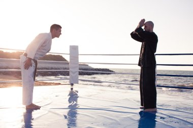 two professional karate fighters in sunrise light