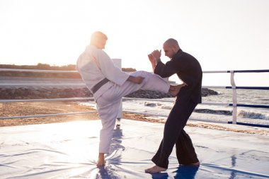 Two professional  karate fighters are fighting on the beach boxing ring
