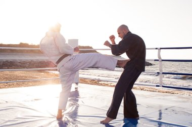 Two professional male karate fighters are fighting on the beach boxing ring