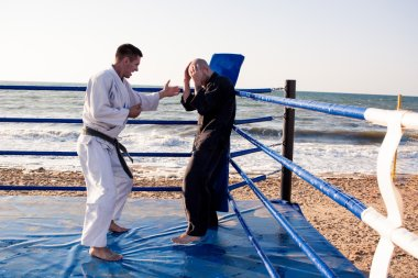 karate sparing on the beach sea background