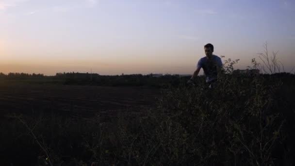 Mladý pes s jízdou na horském kole na kopcích v létě dai proti krásnému západu slunce