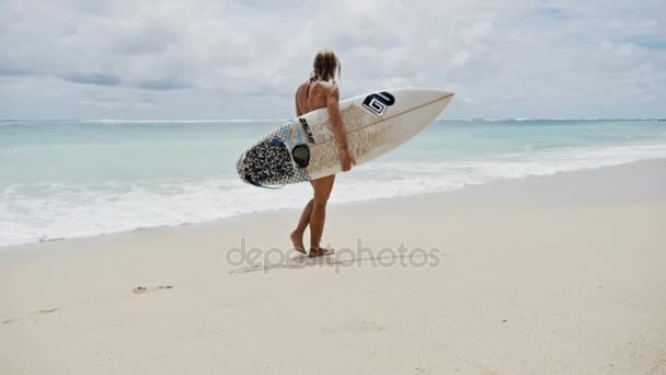girl walking on the beach with her surfboard in her hand