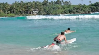 Young Surfers in swimming suit swimming on blue water of ocean in Weligama