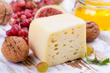 Yellow cheese brick with spices and snacks