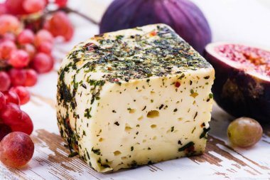 Brick of cow milk cheese with herbs and spices